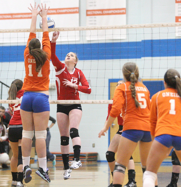 Description of . VVS' Sydney Keenan (12) puts a shot over the net as  Oneida's Matteson Mair (11) defends in the first game of the match at Oneida on Wednesday, Dec. 4, 2013. VVS won the first game 25-18. JOHN HAEGER-ONEIDA DAILY DISPATCH @ONEIDAPHOTO ON TWITTER