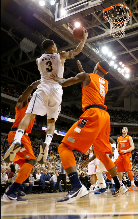 Description of . Pittsburgh's Cameron Wright (3) shoots in front of Syracuse's C.J. Fair (5) during the first half of an NCAA college basketball game on Wednesday, Feb. 12, 2014, in Pittsburgh. (AP Photo/Keith Srakocic)