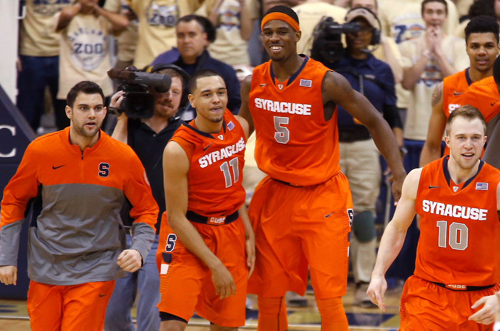 Description of . Syracuse's Tyler Ennis (11) celebrates with teammate C.J. Fair (5) and others after hitting a 3-point shot with less than a second in the NCAA college basketball game against Pittsburgh on Wednesday, Feb. 12, 2014, in Pittsburgh. Syracuse won 58-56. (AP Photo/Keith Srakocic)