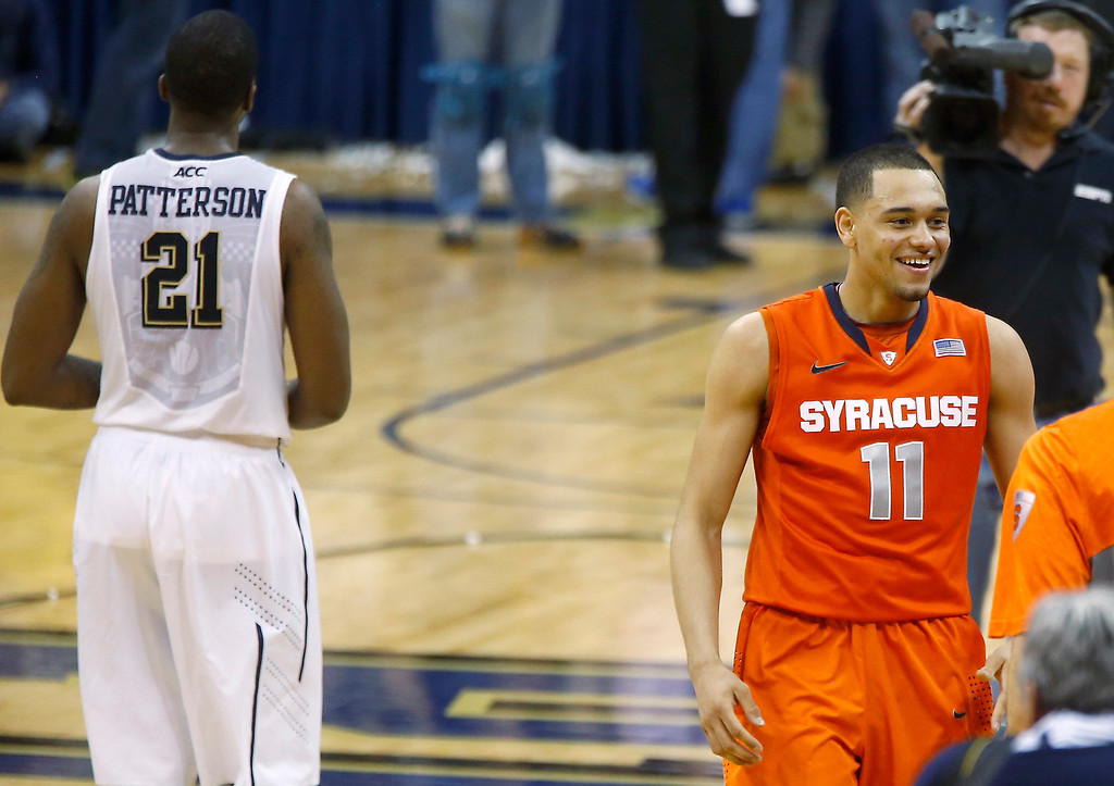Description of . Syracuse's Tyler Ennis (11) smiles as he walks past Pittsburgh's Lamar Patterson (21) after making the game winning shot with time running out in an NCAA college basketball game on Wednesday, Feb. 12, 2014, in Pittsburgh. Syracuse won 58-56. (AP Photo/Keith Srakocic)