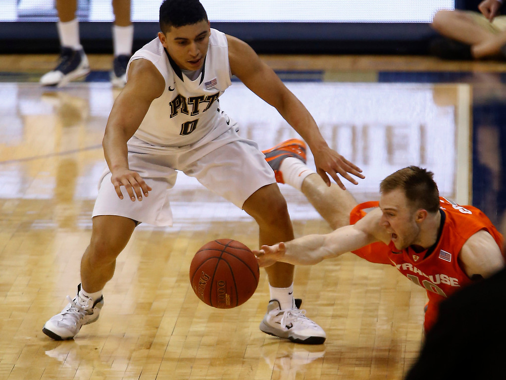Description of . Pittsburgh's James Robinson, left, and Syracuse's Trevor Cooney go for a loose ball during the second half of an NCAA college basketball game Wednesday, Feb. 12, 2014, in Pittsburgh. (AP Photo/Keith Srakocic)