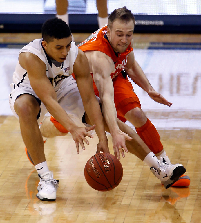 Description of . Pittsburgh's James Robinson, left, and Syracuse's Trevor Cooney go for a loose ball during the second half of an NCAA college basketball game on Wednesday, Feb. 12, 2014, in Pittsburgh. (AP Photo/Keith Srakocic)