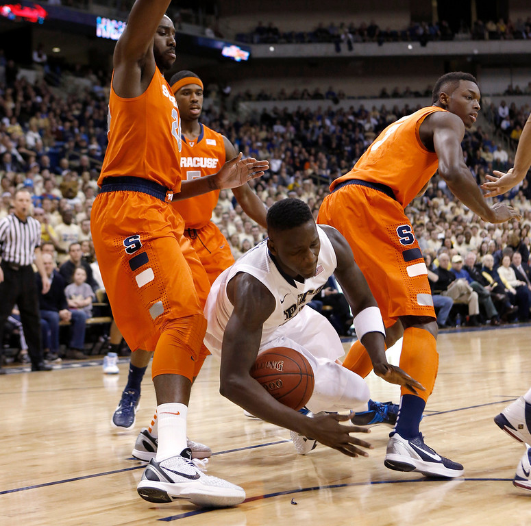 Description of . Pittsburgh's Talib Zanna, center, tumbles between Syracuse's Rakeem Christmas, left, and Jerami Grant, right, during the first half of an NCAA college basketball game Wednesday, Feb. 12, 2014, in Pittsburgh. (AP Photo/Keith Srakocic)