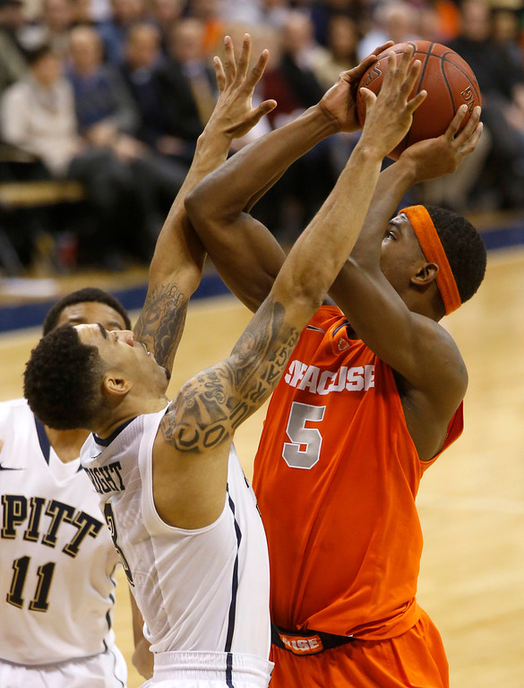Description of . Syracuse's C.J. Fair, right, shoots over Pittsburgh's Cameron Wright during the second half of an NCAA college basketball game on Wednesday, Feb. 12, 2014, in Pittsburgh. (AP Photo/Keith Srakocic)