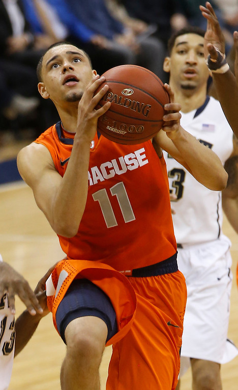 Description of . Syracuse's Tyler Ennis (11) shoots in front of Pittsburgh's Cameron Wright during the second half of an NCAA college basketball game on Wednesday, Feb. 12, 2014, in Pittsburgh. (AP Photo/Keith Srakocic)