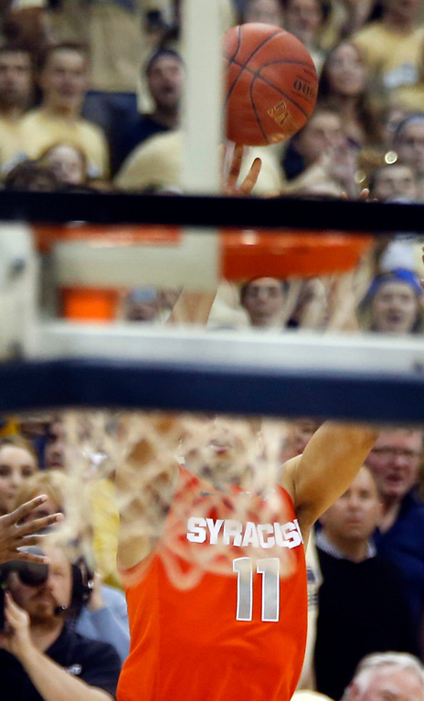Description of . Syracuse's Tyler Ennis (11) is seen through the twine of the net as he shoots a three point shot as time runs down in the second half of an NCAA college basketball game against Pittsburgh on Wednesday, Feb. 12, 2014, in Pittsburgh. The shot went in and Syracuse won 58-56 on the three point shot with less than a second left in the game. (AP Photo/Keith Srakocic)