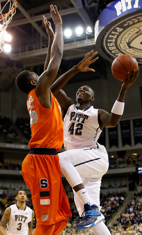 Description of . Pittsburgh's Talib Zanna (42) goes up for a shot as Syracuse's Rakeem Christmas defends during the first half of an NCAA college basketball game Wednesday, Feb. 12, 2014, in Pittsburgh. (AP Photo/Keith Srakocic)