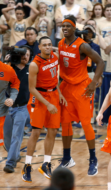 . Syracuse\'s Tyler Ennis (11) celebrates with C.J. Fair (5) after hitting a 3-point shot with less than a second remaining in an NCAA college basketball game against Pittsburgh on Wednesday, Feb. 12, 2014, in Pittsburgh. Syracuse won 58-56. (AP Photo/Keith Srakocic)
