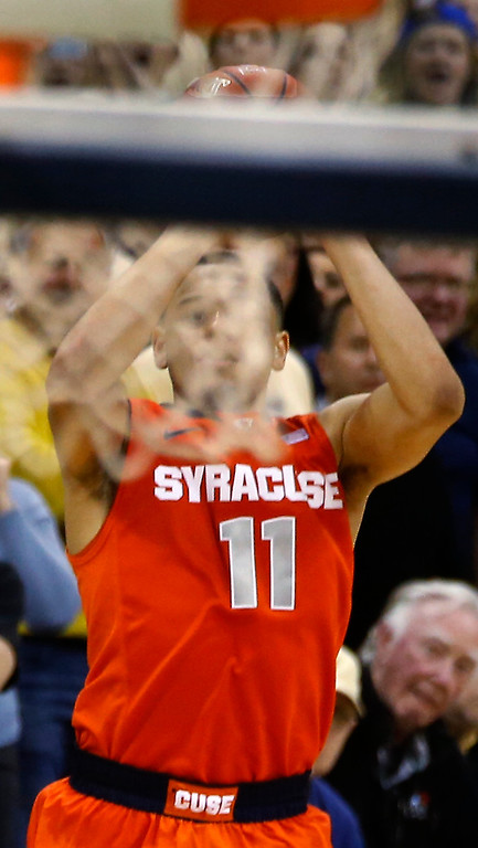 . Syracuse\'s Tyler Ennis (11) is seen through the twine of the net as he shoots a 3-pointer in the final second of an NCAA college basketball game against Pittsburgh on Wednesday, Feb. 12, 2014, in Pittsburgh. The shot went in and Syracuse won 58-56. (AP Photo/Keith Srakocic)