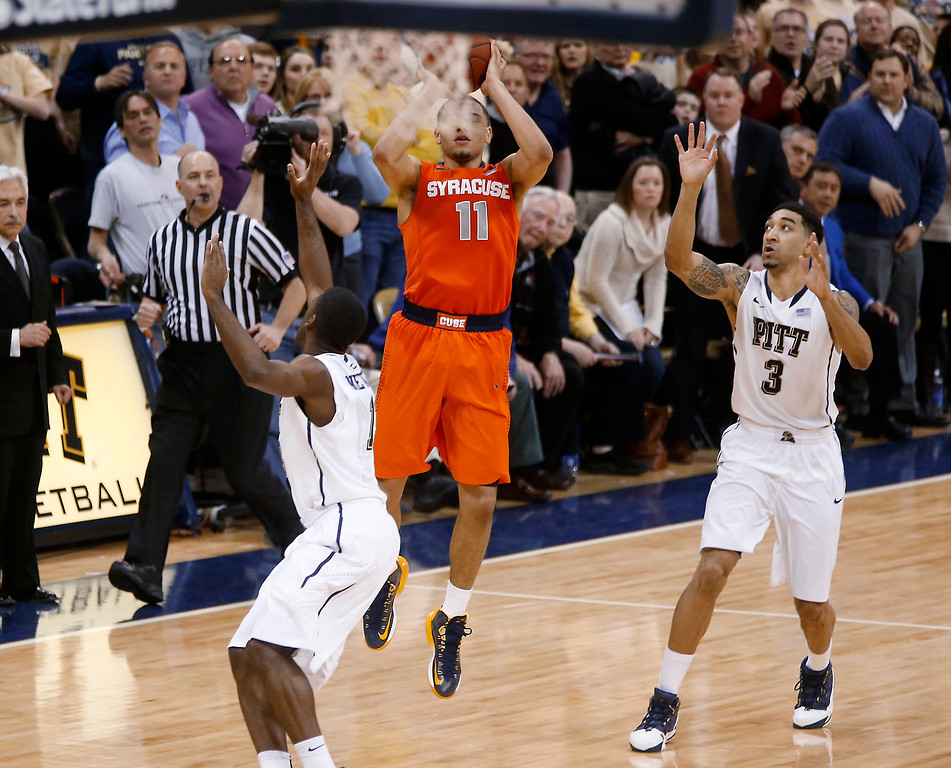 . Syracuse\'s Tyler Ennis (11) shoots 3-pointer between Pittsburgh\'s Cameron Wright (3) and Josh Newkirk, left, in the final second of an NCAA college basketball game Wednesday, Feb. 12, 2014, in Pittsburgh. The shot went in and Syracuse won 58-56. (AP Photo/Keith Srakocic)
