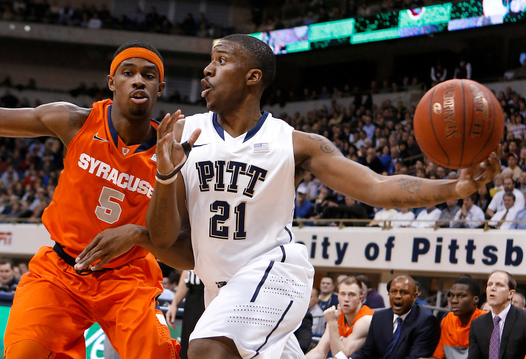 . Pittsburgh\'s Lamar Patterson (21) passes as Syracuse\'s C.J. Fair (5) defends during the first half of an NCAA college basketball game Wednesday, Feb. 12, 2014, in Pittsburgh. (AP Photo/Keith Srakocic)